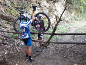 Two mountain bikers are lifting their rental MTB over a fence