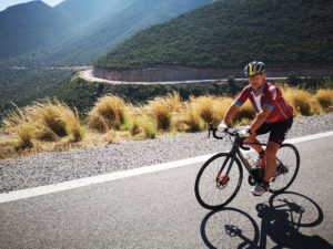 Road cyclist along a perfect coastal road in the Peloponnese
