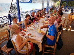 Road cyclists enjoy a meal at fish tavern after their ride in the Peloponnese