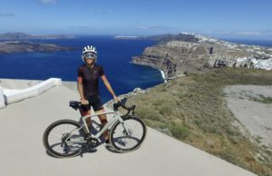 Female cyclist in front of the wide open view of Santorini caldera