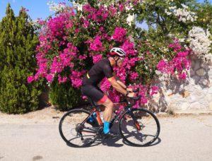 Road Cyclist in front of a Bougainvillea enroute to Porto Cheli