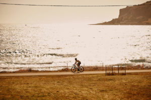Road cyclist is cycling along the coast with bright sea colours